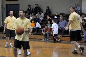 Adults playing basketball in a gym.